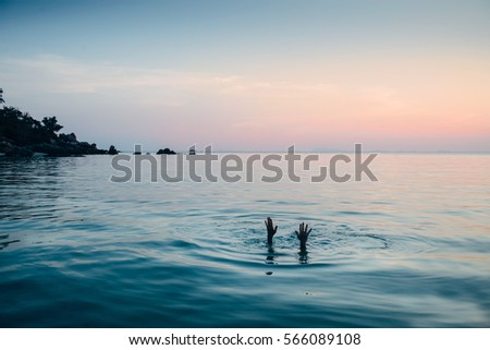 Man exploring the depth of the sea on sunset. Dive under the water and show hands on the surface..