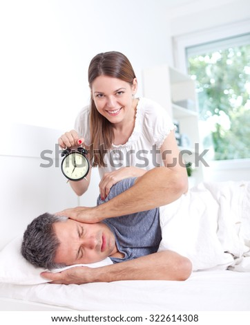 Man extremely annoyed by the alarm clock, shallow depth of field - stock photo