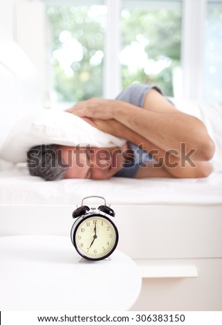 Man extremely annoyed by the alarm clock, shallow depth of field, focus on foreground - stock photo