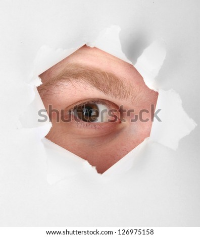 Man eye looking through hole in sheet of paper - stock photo