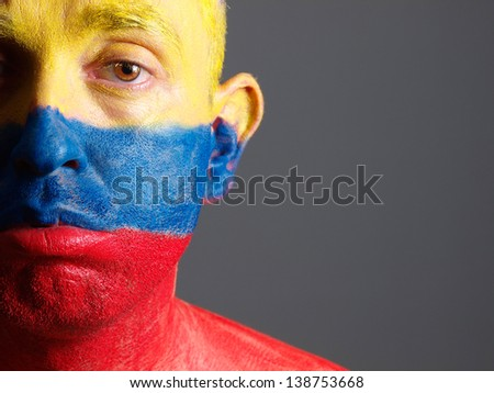 Man face painted with colombian flag. The man is sad and photographic composition leaves only half of the face. - stock photo