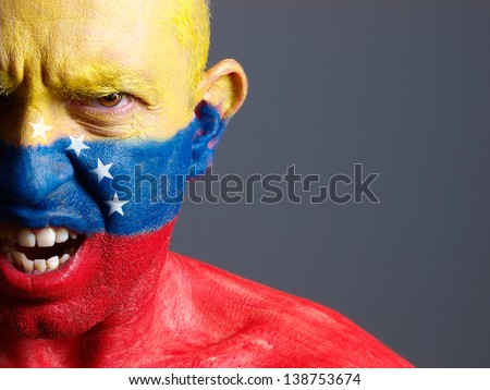 Man face painted with venezuelan flag. The man is angry and photographic composition leaves only half of the face. - stock photo