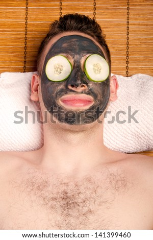 Man face with beauty treatment skincare mask and cucumber laying on bamboo at spa. - stock photo