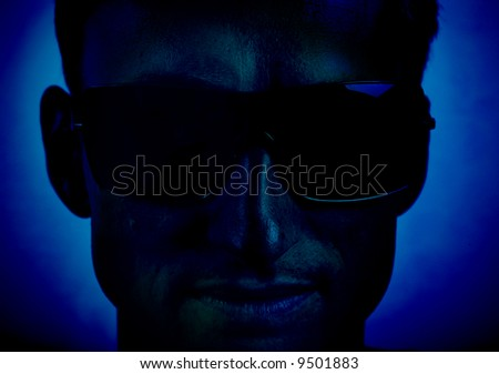 man face with sunglasses in dark blue - stock photo