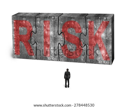 Man facing red risk word on four huge concrete puzzles connected together, isolated on white background - stock photo
