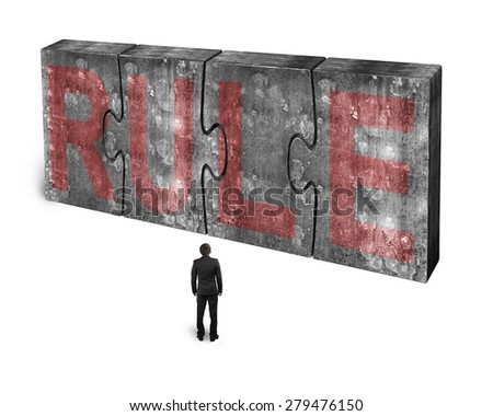 Man facing red rule word on four huge concrete puzzles connected together, isolated on white background - stock photo