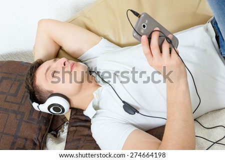 Man fall asleep listening to music over smartphone with headphones , Handsome guy lying on sofa holding mobile phone and listening to music over headset - stock photo