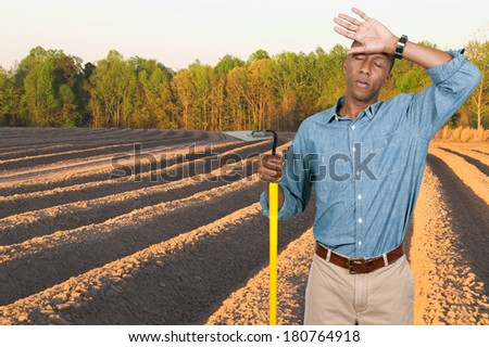 Man farmer with a hoe in the furrows of a freshly plowed field - stock photo