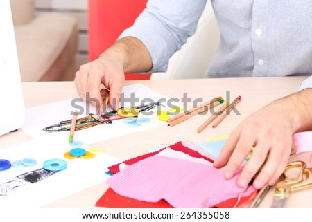 Man fashion designer draws sketches of new collection - stock photo