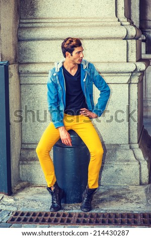 Man Fashion. Dressing in a blue jacket with hood, black underwear, yellow pants, leather boot shoes, a young handsome guy is sitting on a metal stake on the corner, looking around, waiting for you.