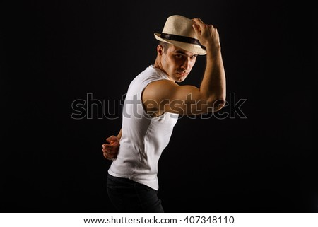 Man fashion model, stylish young man wearing fedora hat standing posing, over black background - stock photo