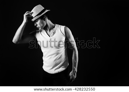 Man fashion model, stylish young man wearing fedora hat standing posing, over black background. Black and white photo. - stock photo