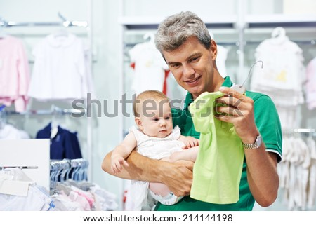 man father choosing shirt with daughter little baby girl during shopping at garments shop - stock photo