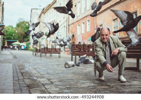 Man feeding pigeons in the old town