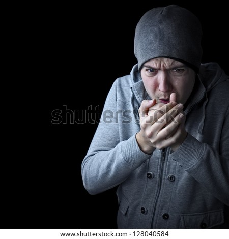 man feeling cold warming hands black and white with copy space - stock photo