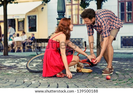 man fell down from the bicycle and woman help him to collect products