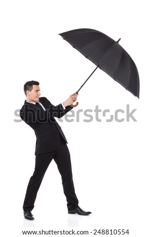 Man fighting with an umbrella. Elegance man holding an open umbrella. Full length studio shot isolated on white. - stock photo