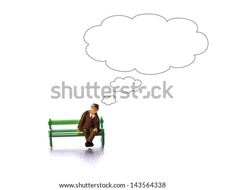 Man figurine on bench thinking - stock photo