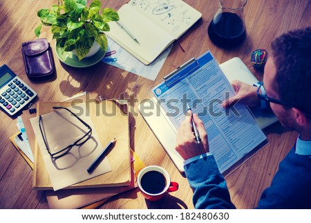 Man Filing Out An Application On Wooden Table - stock photo