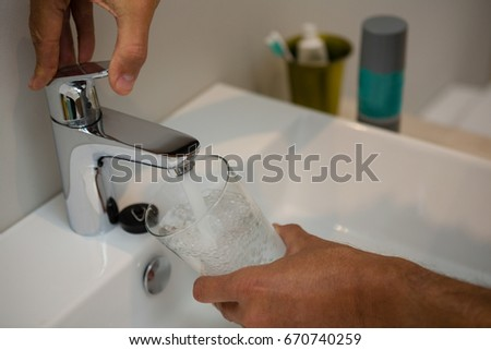 Man Filling Glass Of Water At Sink In Bathroom