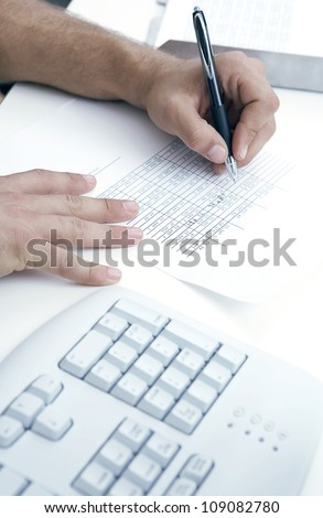 Man filling in data on a page of tabulated statistics by hand with a pen
