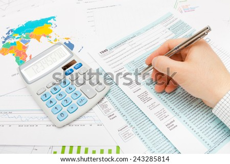 Man filling out 1040 US Tax Form - stock photo