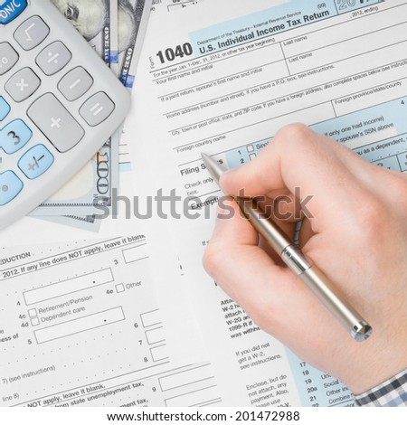 Man filling out 1040 US Tax Form - view from top - 1 to 1 ratio - stock photo