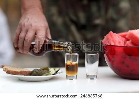 Man fills glasses of brandy at picnic - stock photo