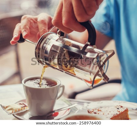 Man fills his cup with tee from the teapot - stock photo