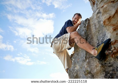 Man finding a foothold while climbing down a steep piece of mountain with copyspace - stock photo