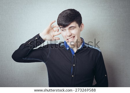 Man finger in the ear, earache, ear hurts. On a gray background. - stock photo