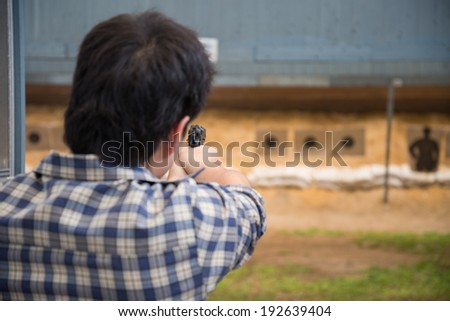 man firing gun to target - stock photo