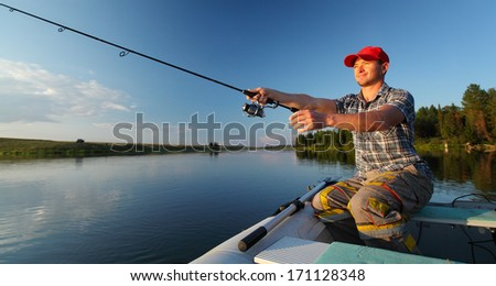Man fishing from a boat at sunset - stock photo