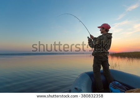 Man fishing from the boat on the lake at sunset - stock photo