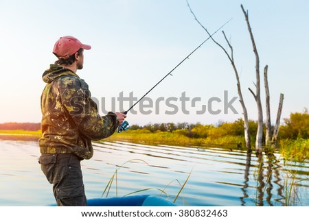 Man fishing from the boat on the lake at sunset