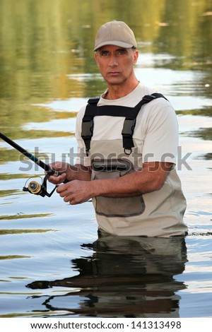 Man fishing in a river - stock photo
