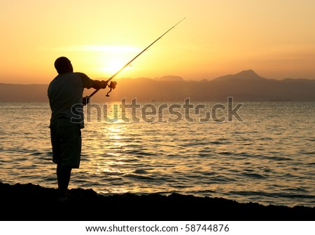 Man fishing in last rays of sunlight on sea shore - stock photo