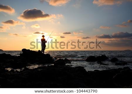 Man fishing in last rays of sunlight on sea shore,Thailand - stock photo