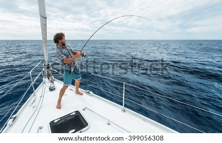 Man fishing in the sea from the boat - stock photo