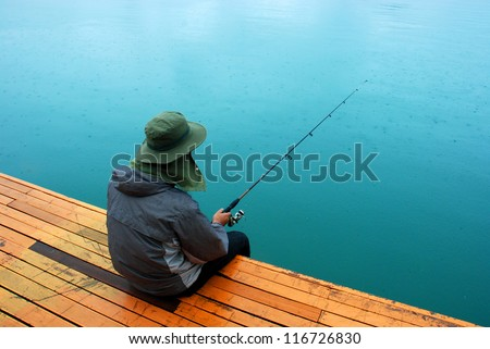 Man fishing near lake from wooden jetty - stock photo