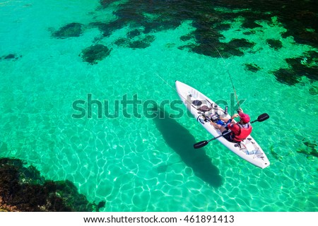 Man fishing on a kayak in the sea with clear turquoise water. Fisherman kayaking in the islands. Leisure activities on the ocean.