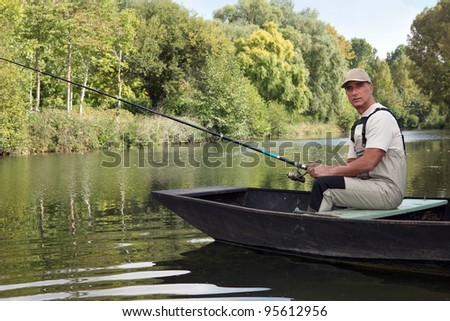 Man fishing on a lake - stock photo