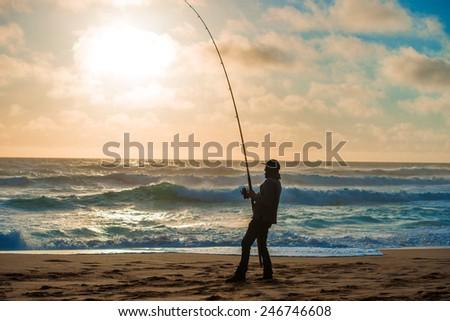 Man fishing on Beach at Sunset - stock photo