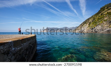 Man fishing on pier in village of Vernazza in Cinque Terre, Italy