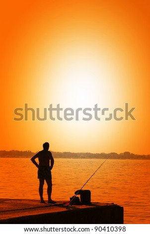 man fishing on the pier at sunset
