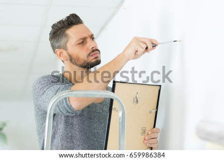 man fitting a frame on the wall