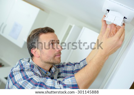 Man fitting an air vent - stock photo
