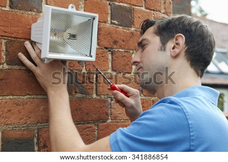 Man Fitting Security Light To Wall Of House - stock photo