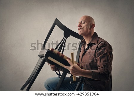 Man fixing a wooden chair - stock photo