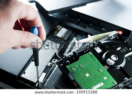 man fixing computer or laptop or notebook with crewdriver - stock photo